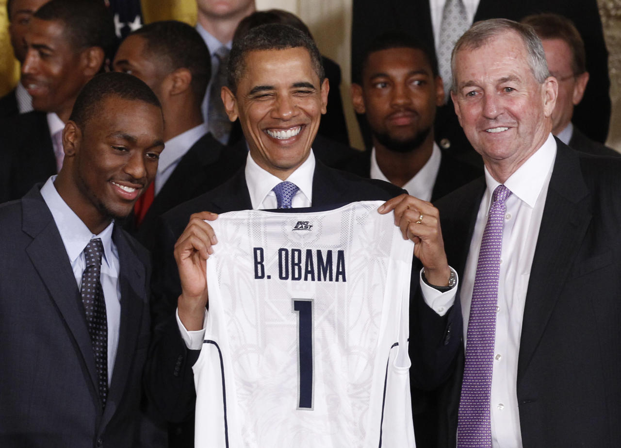 U.S. President Barack Obama is presented with a jersey from Kemba Walker (L) and coach Jim Calhoun (R) at a ceremony honoring the 2011 NCAA men's basketball champions University of Connecticut at the White House in Washington, May 16, 2011.   REUTERS/Jim Young   (UNITED STATES - Tags: SPORT BASKETBALL POLITICS)