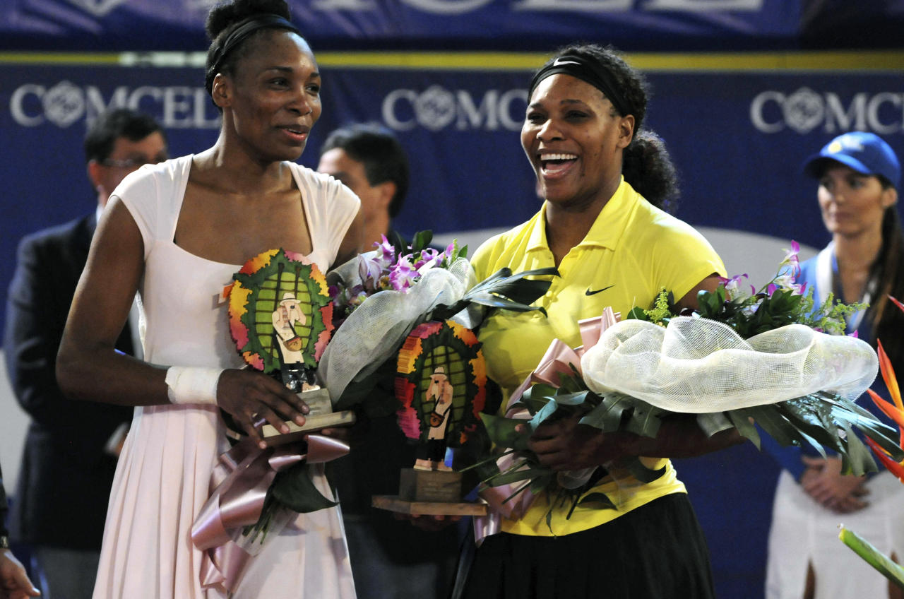 Venus Williams, left, and her sister Serena Williams hold trophies after an exhibition tennis match in Medellin, Colombia, Wednesday Nov. 23, 2011. Venus made her comeback defeating her sister 6-4, 7-6, two months after pulling out of the U.S. Open because of an immune system disease. (AP Photo/Luis Benavides)