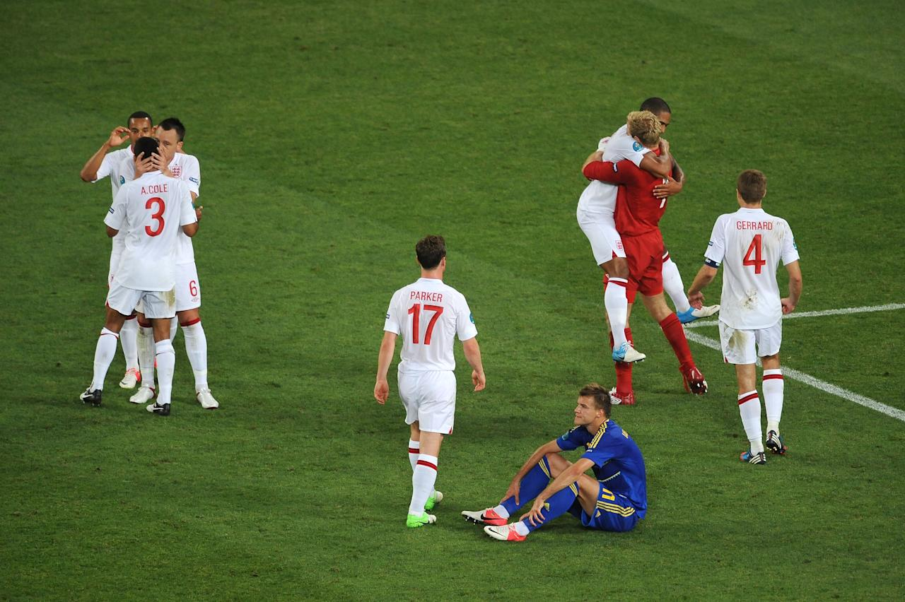 DONETSK, UKRAINE - JUNE 19:  Andriy Yarmolenko of Ukraine sits dejected as England players celebrate victory during the UEFA EURO 2012 group D match between England and Ukraine at Donbass Arena on June 19, 2012 in Donetsk, Ukraine.  (Photo by Christopher Lee/Getty Images)