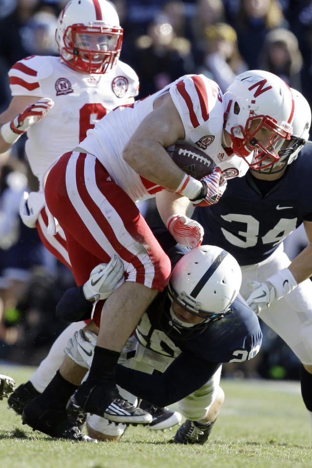 Penn State safety Drew Astorino, bottom, tackles Nebraska running back Rex Burkhead during the second quarter of an NCAA college football game in State College, Pa., Saturday, Nov. 12, 2011. (AP Photo/Gene J. Puskar)