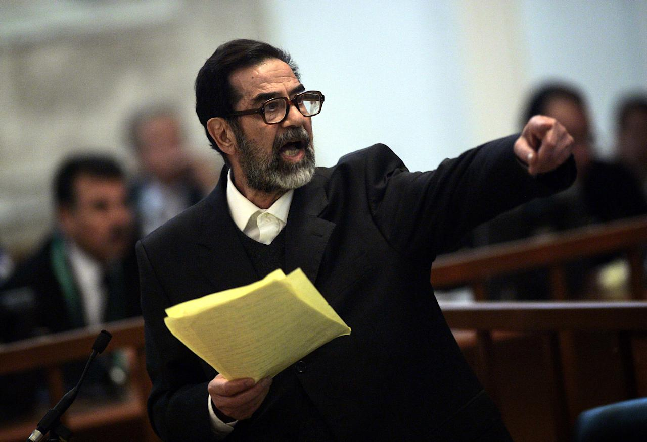 Former Iraqi President Saddam Hussein argues with prosecutors while testifying during cross-examination at his trial in Baghdad's Green Zone April 5, 2006. Hussein returned to court on Wednesday and, in remarks likely to inflame sectarian tensions, immediately accused the Iraqi Interior Ministry of killing and torturing thousands of Iraqis.     REUTERS/David Furst/Pool