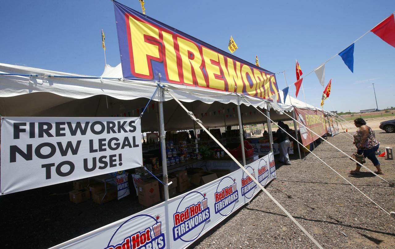 In this photo taken on Wednesday, July 2, 2014, customers walk into a Red Hot Fireworks tent in Phoenix. Although Phoenix has gone a full 120 days without any measurable precipitation there has not been any serious effort in the drought-stricken states to restrict fireworks. Arizona actually loosened its restrictions this year and allowed residents of the two most populated cities to set off fireworks around Independence Day. (AP Photo/Ross D. Franklin)