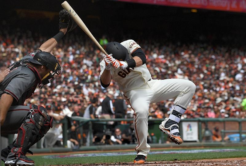 Buster Posey of the San Francisco Giants falls backwards after he was hit in the head with a pitch by Taijuan Walker of the Arizona Diamondbacks in the bottom of the first inning at AT&T Park