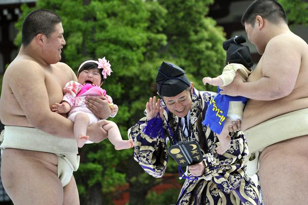 "Student sumo wrestlers carry crying babies during the ""Baby-cry Sumo"" competition at Tokyo's Sensoji temple on April 30, 2011.  Some 50 babies aged under one participated in the annual baby crying contest. Japanese parents believe that sumo wrestlers can help make babies cry out a wish to grow up with good health.   AFP PHOTO/Yoshikazu TSUNO"