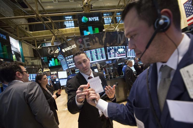 Traders use a paper trading slip on the floor of the New York Stock Exchange