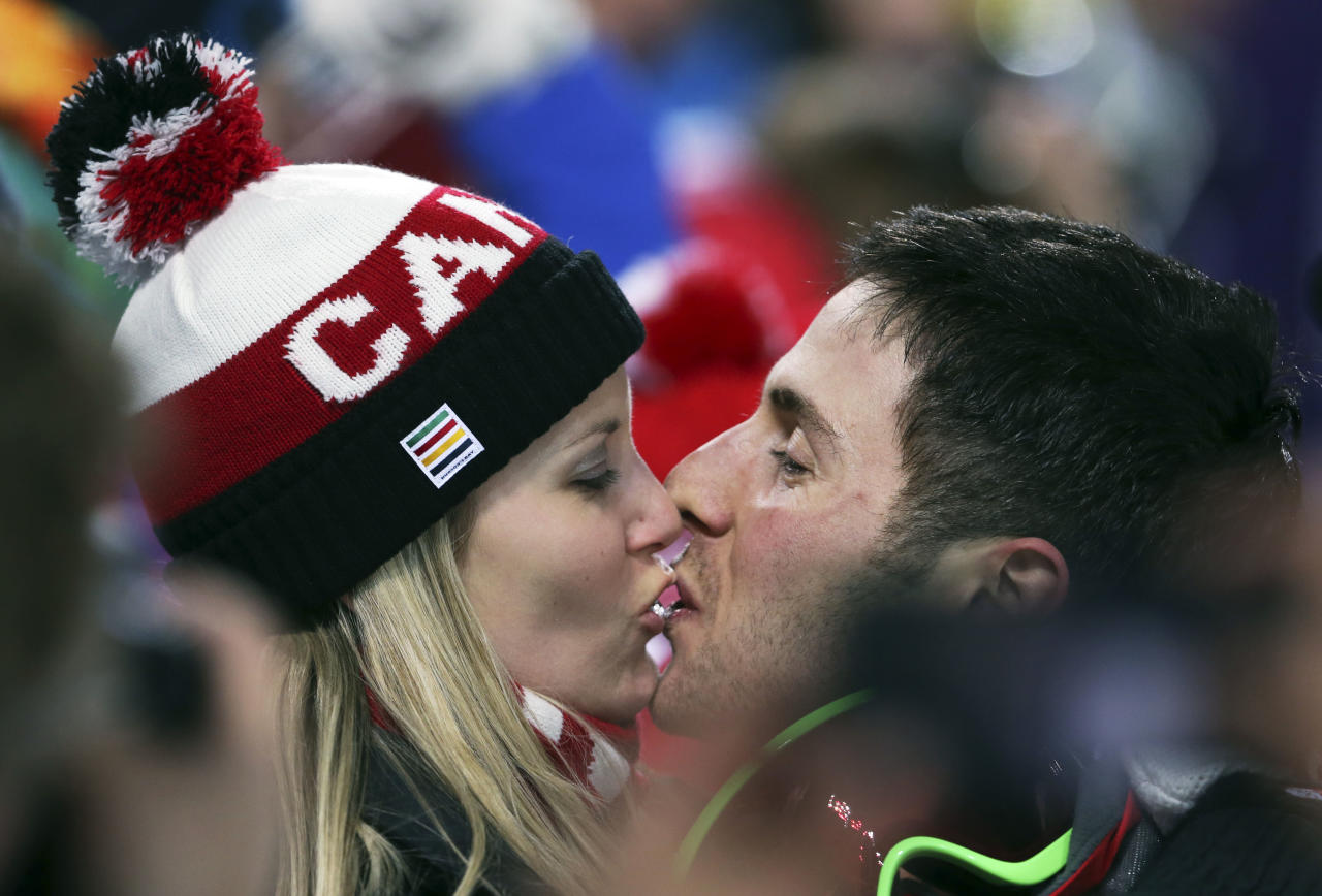 Canada's Alex Bilodeau, right, kisses his girlfriend Sabrina after he won the gold medal in the men's moguls final at the 2014 Winter Olympics, Monday, Feb. 10, 2014, in Krasnaya Polyana, Russia. (AP Photo/Sergei Grits)