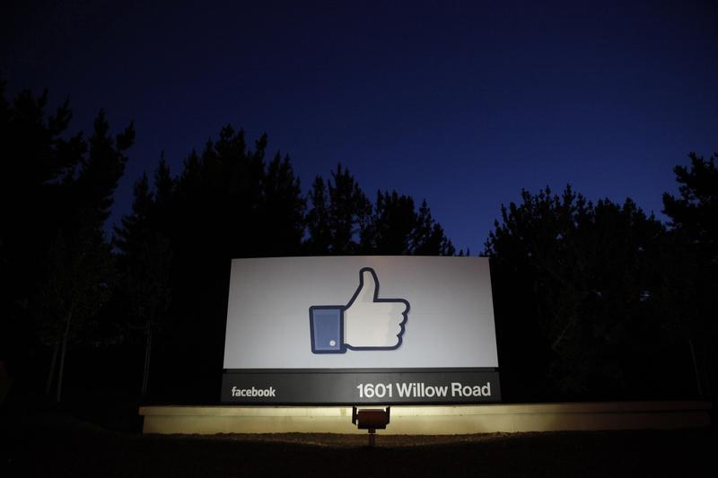 The sun rises behind the entrance sign to Facebook headquarters in Menlo Park before the company's IPO launch,
