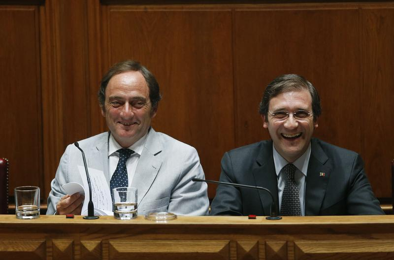 Portugal's Prime Minister Pedro Passos Coelho and Deputy Prime Minister Paulo Portas smile during the debate to vote on a motion of confidence in Lisbon