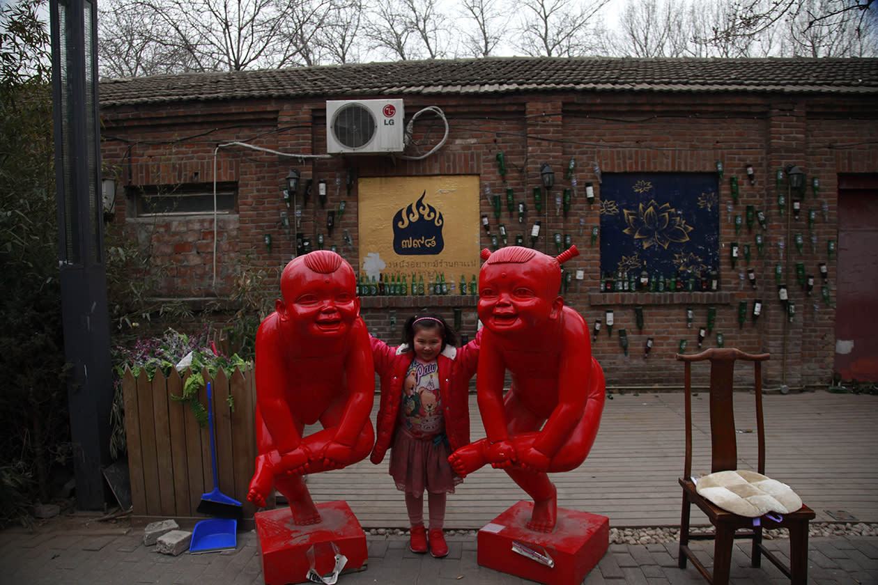 A child poses for photos near sculptures displayed at the 798 art district.