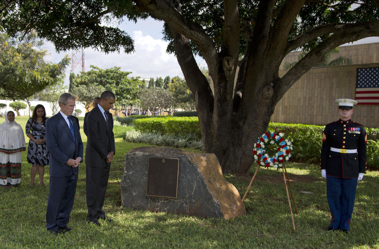 U.S. President Barack Obama and former U.S. President George W. Bush pause for a moment of silence during a wreath laying ceremony to honor the victims of the U.S. Embassy bombing on Tuesday, July 2, 2013, in Dar Es Salaam, Tanzania. The president is traveling in Tanzania on the final leg of his three-country tour in Africa. (AP Photo/Evan Vucci)