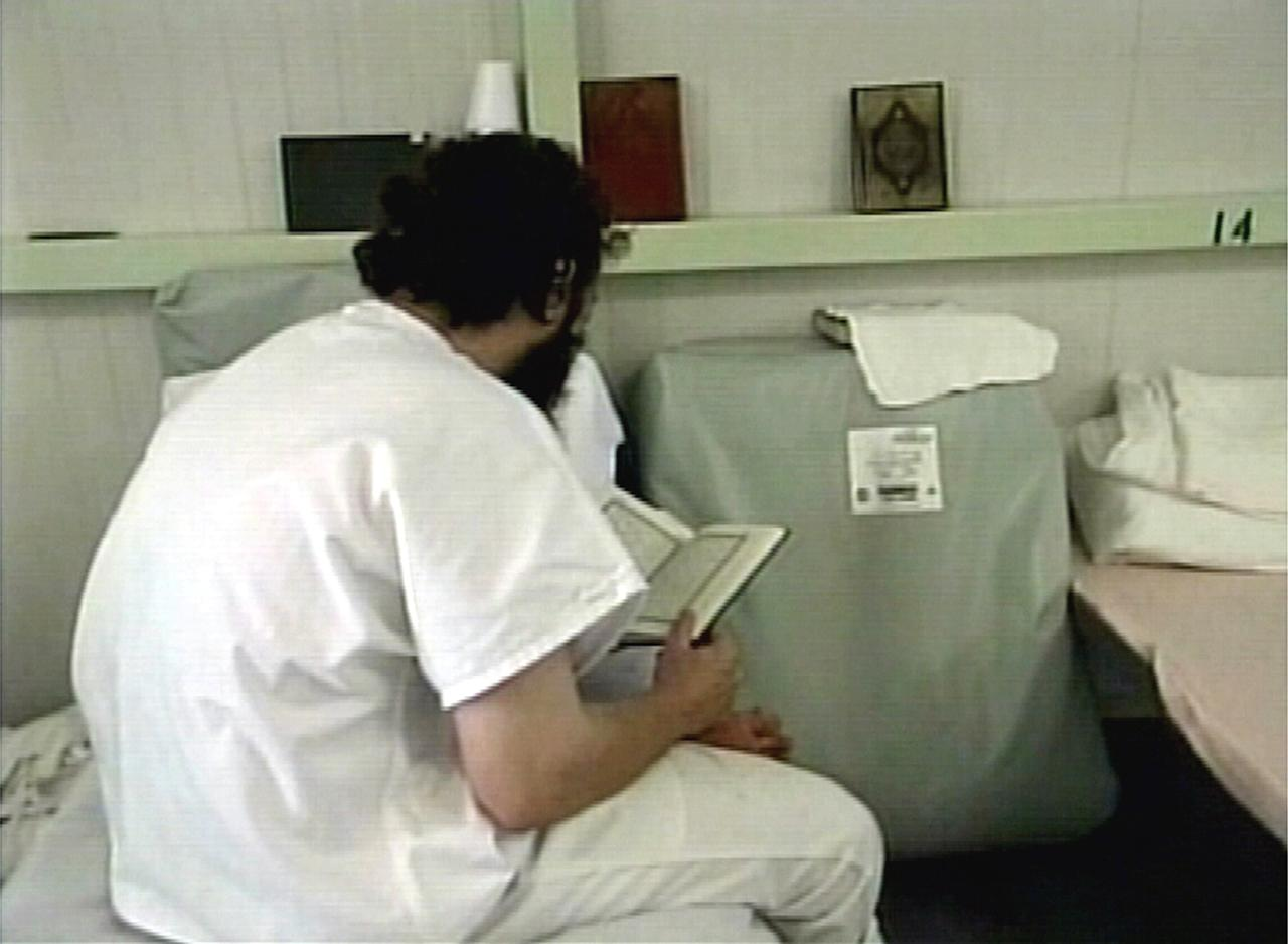 A frame grab taken from undated video footage, released by the U.S. Department of Defence February 5, 2004, shows a minimum security detainee sitting on a cot bed reading a copy of the Koran inside the military detention facility at the U.S naval base at Guantanamo Bay, Cuba. REUTERS/DOD Handout  AA