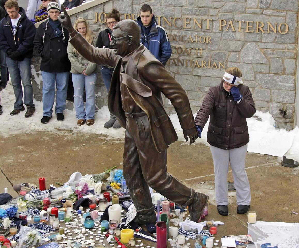 A woman pays her respects at a statue of Joe Paterno outside Beaver Stadium on the Penn State University campus after learning of his death Sunday, Jan. 22, 2012 in State College, Pa. (AP Photo/Gene J. Puskar)