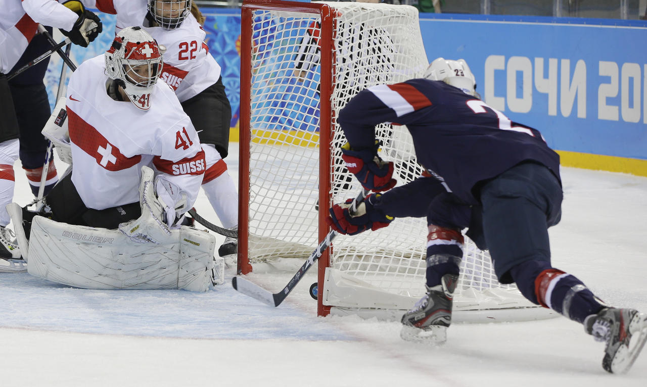Goalkeeper Florence Schelling of Switzerland watches as Amanda Kessel of the Untied States shoot slides in for the goal during the first period of the 2014 Winter Olympics women's ice hockey game at Shayba Arena, Monday, Feb. 10, 2014, in Sochi, Russia. (AP Photo/Matt Slocum)
