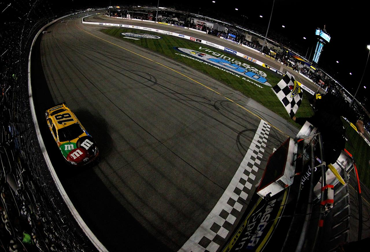 RICHMOND, VA - APRIL 28:  Kyle Busch, driver of the #18 M&M's Ms. Brown Toyota, takes the checkered flag to win the NASCAR Sprint Cup Series Capital City 400 at Richmond International Raceway on April 28, 2012 in Richmond, Virginia.  (Photo by Tyler Barrick/Getty Images for NASCAR)