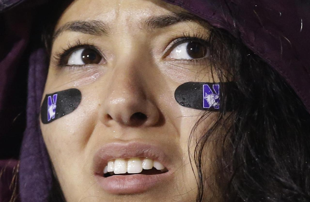 A Northwestern fan reacts as she looks at the scoreboard during the second half of Northwestern's NCAA college football game against Michigan in Evanston, Ill., Saturday, Nov. 16, 2013. Michigan won 27-19. (AP Photo/Nam Y. Huh)