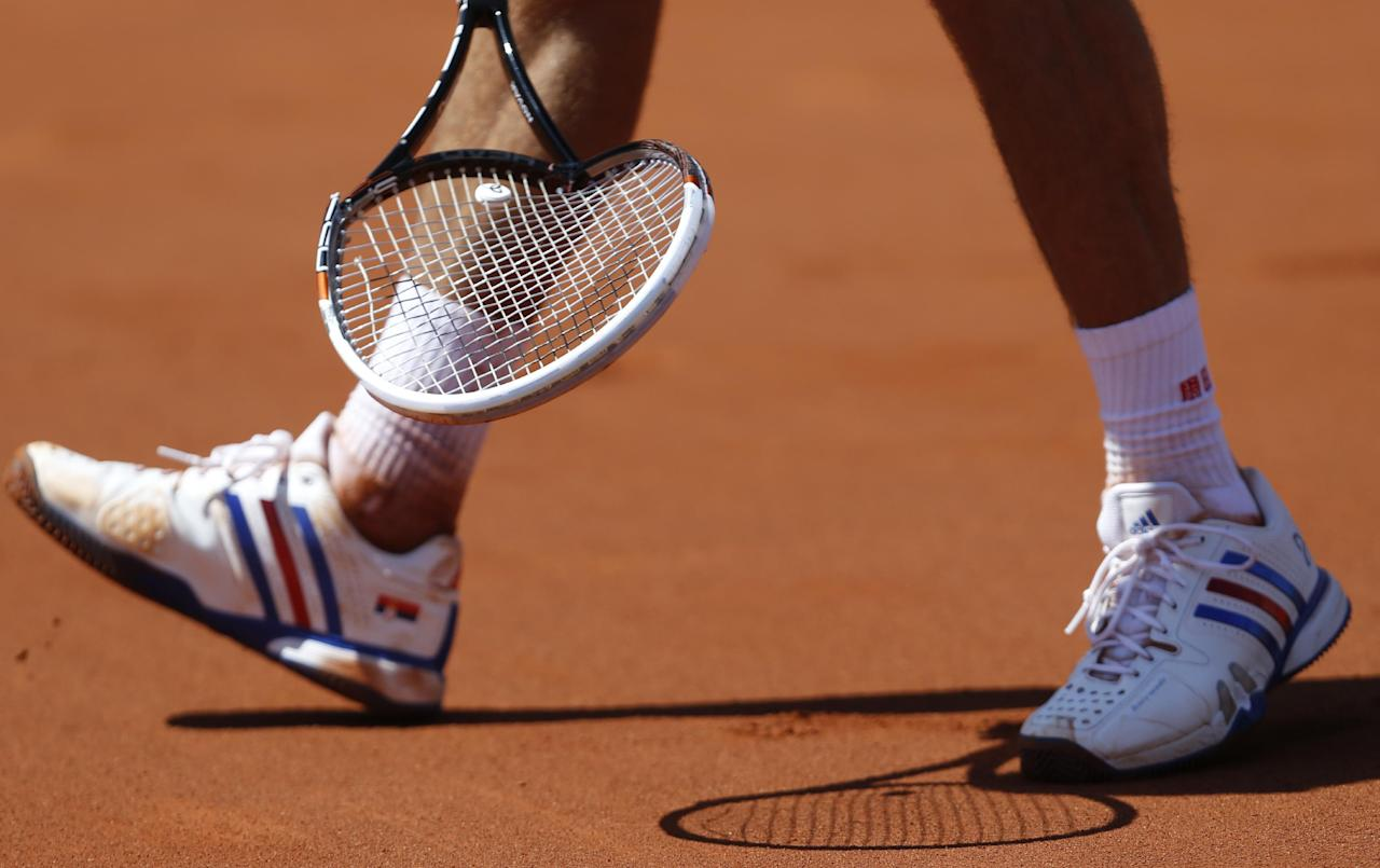 Serbia's Novak Djokovic picks up the racket he smashed on the court during the semifinal match of the French Open tennis tournament against Latvia's Ernests Gulbis at the Roland Garros stadium, in Paris, France, Friday, June 6, 2014. Djokovic won in four sets 6-3, 6-3, 3-6, 6-3. (AP Photo/Darko Vojinovic)