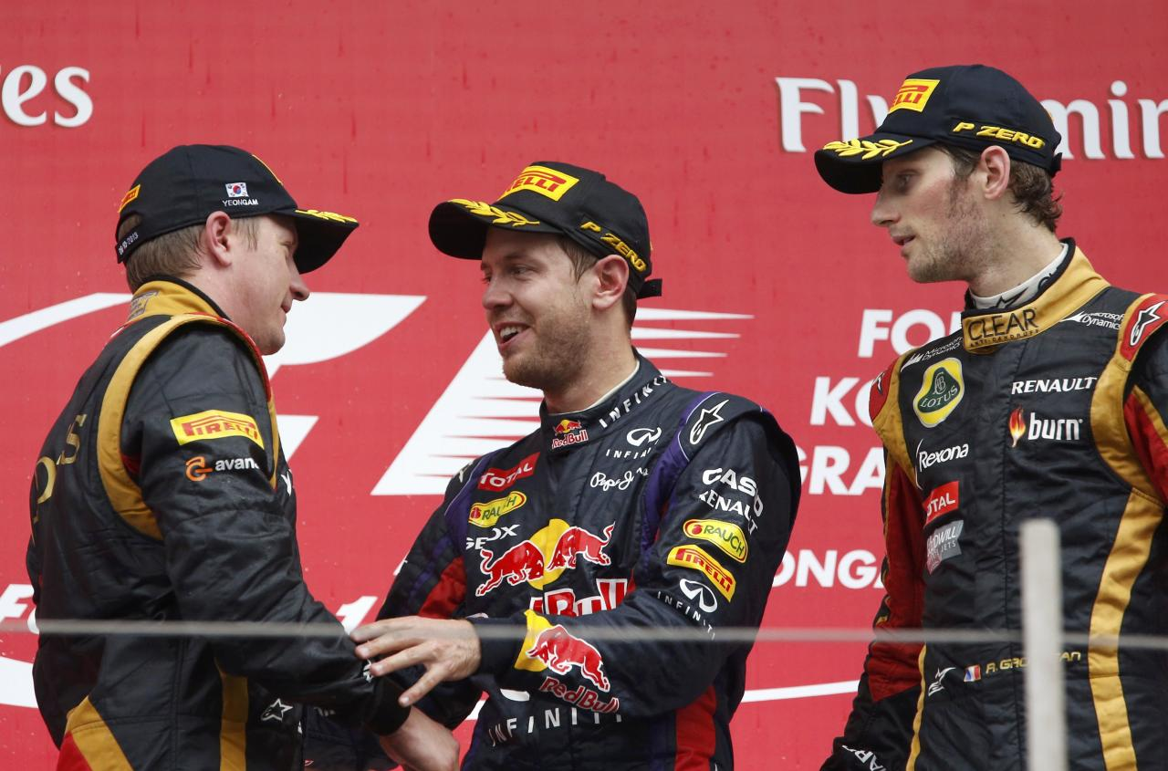 Winner Red Bull Formula One driver Sebastian Vettel of Germany (C) speaks to second placed Lotus Formula One driver Kimi Raikkonen of Finland (L) as third placed Lotus Formula One driver Romain Grosjean of France looks on after the Korean F1 Grand Prix at the Korea International Circuit in Yeongam, October 6, 2013. REUTERS/Kim Hong-Ji (SOUTH KOREA - Tags: SPORT MOTORSPORT F1)