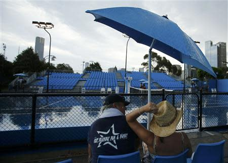 Spectators wait for a storm to pass before play on courts outside start again at the Australian Open 2014 tennis tournament in Melbourne