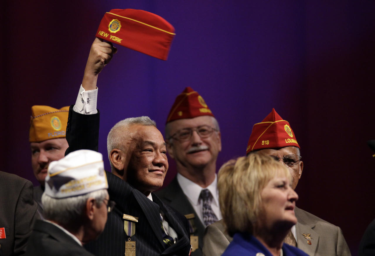 David J. Louie, National Sergeant-At-Arms of The American Legion spins his hat on his finger before Republican presidential candidate, former Massachusetts Gov. Mitt Romney was introduced at the American Legionís national convention in Indianapolis, Wednesday, Aug. 29, 2012. (AP Photo/Michael Conroy)