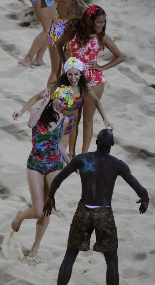 Dancers perform at the Beach Volleyball Venue at the 2012 Summer Olympics, Saturday, July 28, 2012, in London. (AP Photo/Dave Martin)