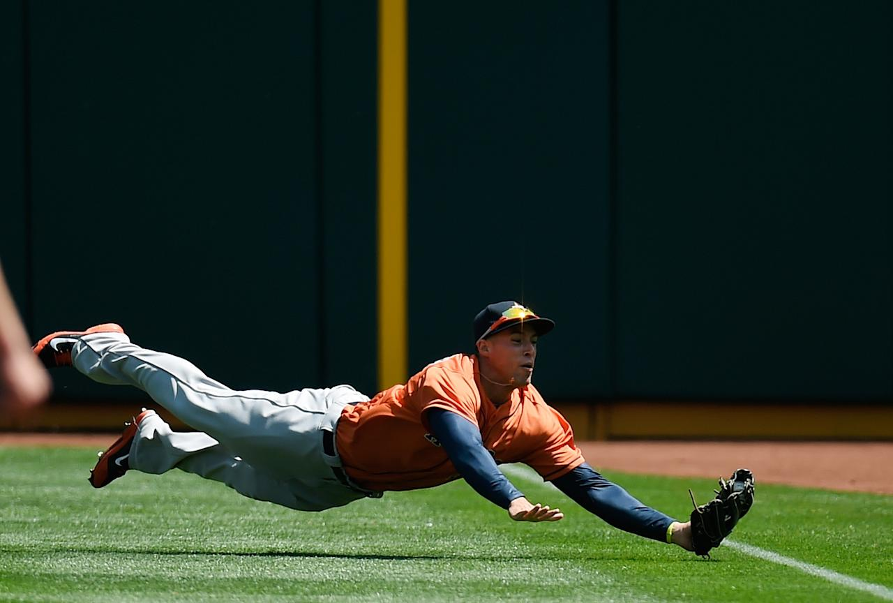 OAKLAND, CA - APRIL 20: George Springer #4 of the Houston Astros dives and takes a hit away from Coco Crisp #4 of the Oakland Athletics (not pictured) in the bottom of the first inning at O.co Coliseum on April 20, 2014 in Oakland, California. (Photo by Thearon W. Henderson/Getty Images)