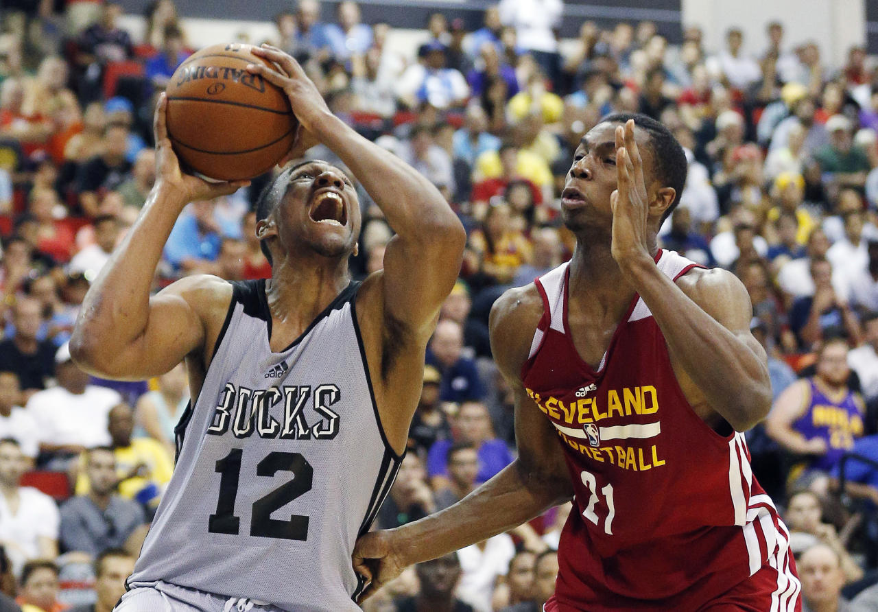 Jabari Parker (12) of the Milwaukee Bucks drives by Andrew Wiggins of the Cleveland Cavaliers in an NBA summer league basketball Friday, July 11, 2014, in Las Vegas. (AP Photo/John Locher)