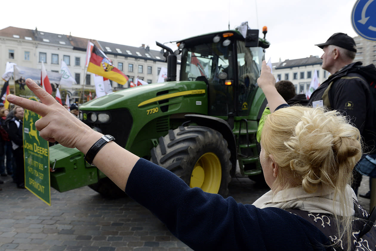 A woman cheers on European milk farmers as they drive their tractors into the European quarter in Brussels.