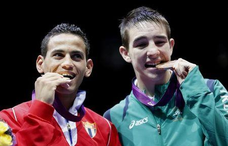 Gold medallist Robeisy Ramirez Carrazana of Cuba (L) and bronze medallist Michael Conlan of Ireland (R) bite their medals during the presentation ceremony for the Men's Fly (52kg) boxing competition at the London Olympics August 12, 2012. REUTERS/Murad Sezer/Files