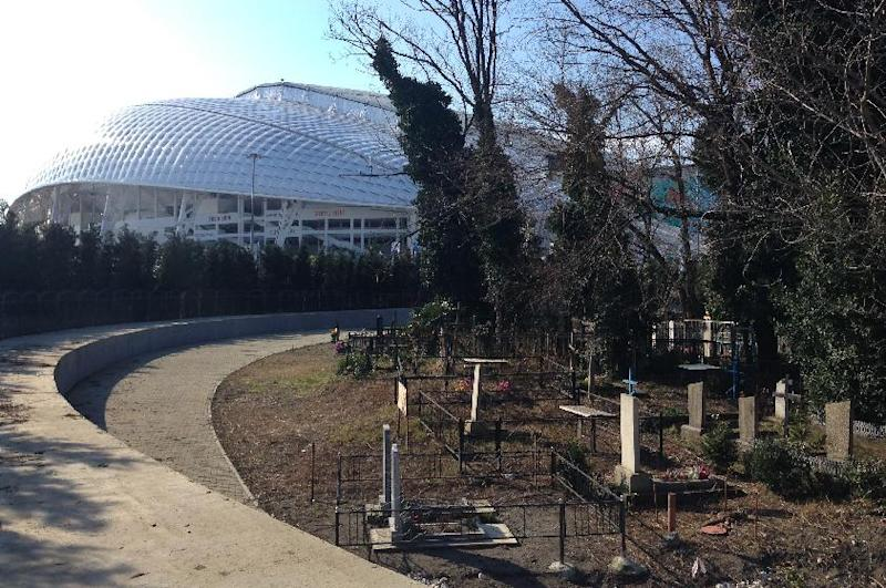 A small cemetery of Old Believers, a purist sect that branched out of the Russian Orthodox in the 17th century, is right in the middle of Olympic Park at the 2014 Winter Olympics in Sochi, Russia, Monday, Feb. 10, 2014. It goes completely unnoticed by passers-by who walk along a round plot of land surrounded by a tinted glass fence and lined with almost identical fir-trees