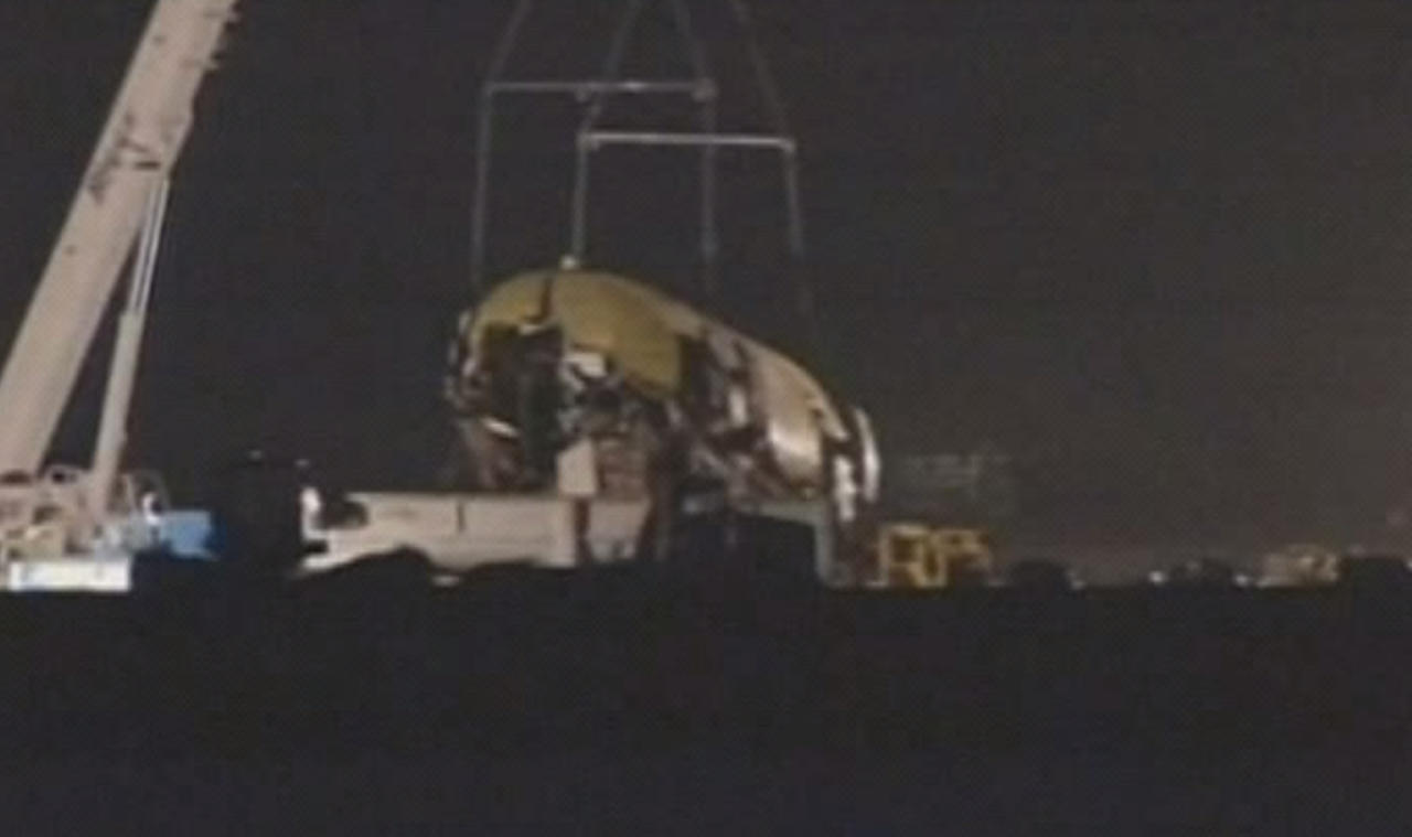 In this image from video provided by ABC7 News/KGO-TV a section of the fuselage of Asiana Flight-214 is removed at San Francisco airport early Friday morning July 12, 2013. Workers began clearing the wreckage early Friday. The Asiana flight crashed upon landing Saturday, July 6, at San Francisco International Airport, and two of the 307 passengers aboard were killed. (AP Photo/ABC7 News/KGO-TV)