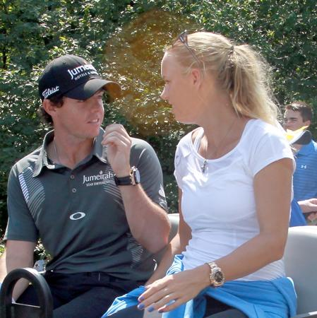 NORTON, MA - SEPTEMBER 01:  Rory McIlroy of Northern Ireland is on the back of a golf cart with tennis player Caroline Wozniacki of Denmark after McIlroy completes his second round of the Deutsche Bank Championship at TPC Boston on September 1, 2012 in Norton, Massachusetts.  (Photo by Jim Rogash/Getty Images)