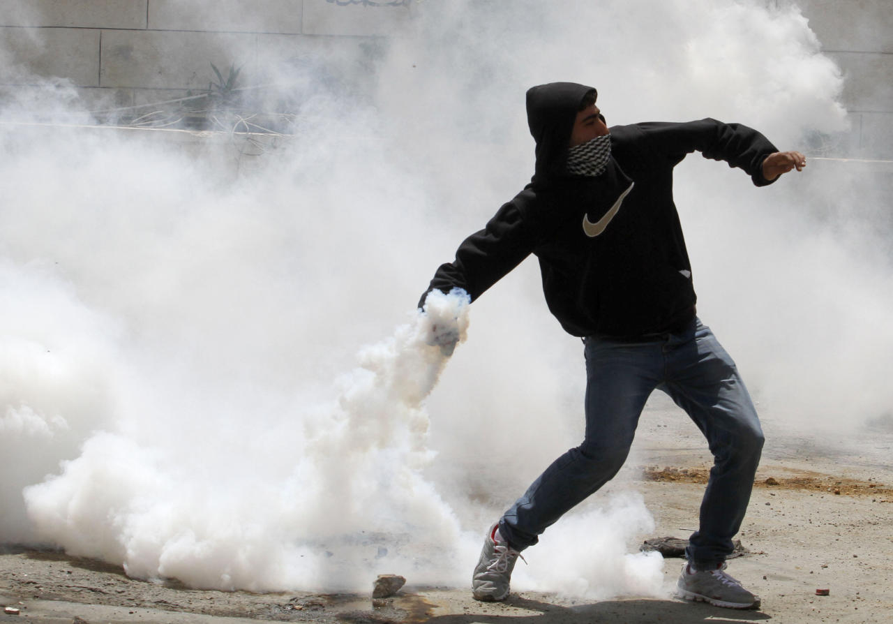 "A masked Palestinian throws back a tear gas canister during clashes after a rally marking the Nakba Day outside the West Bank town of Hebron, Wednesday , May 15, 2013. Palestinians annually mark the ""nakba,"" or ""catastrophe"" the term they use to describe their defeat and displacement in the war that followed Israel's founding in 1948. (AP Photo/Nasser Shiyoukhi)"