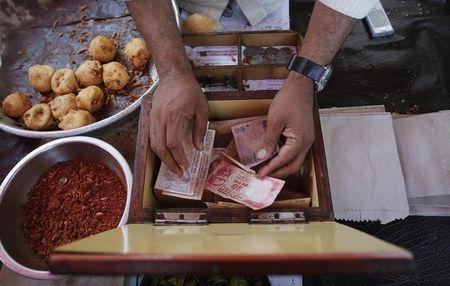 A streetside restaurant owner keeps money received from a customer in Mumbai