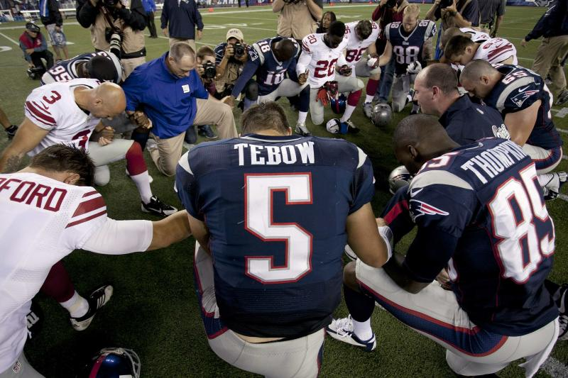 New England Patriots quarterback Tim Tebow prays with his teammates and members of the New York Giants after their NFL preseason game in Foxborough, Massachusetts, August 29, 2013. REUTERS/Dominick Reuter (UNITED STATES - Tags: SPORT FOOTBALL)