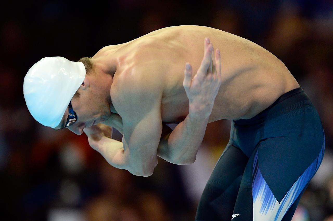 Michael Phelps stretches prior to swimming in preliminary heat 12 of the Men's 200 m Freestyle during Day Two of the 2012 U.S. Olympic Swimming Team Trials at CenturyLink Center on June 26, 2012 in Omaha, Nebraska.  (Photo by Jamie Squire/Getty Images)