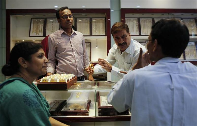 An employee shows gold bangles to a customer at jewellery showroom on the occasion of Dhanteras, a Hindu festival associated with Lakshmi, the goddess of wealth, at a market in Mumbai November 1, 2013.