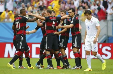Germany's Mueller celebrates after scoring a goal with teammates as Besler of the U.S. walks past during their 2014 World Cup Group G soccer match at the Pernambuco arena in Recife