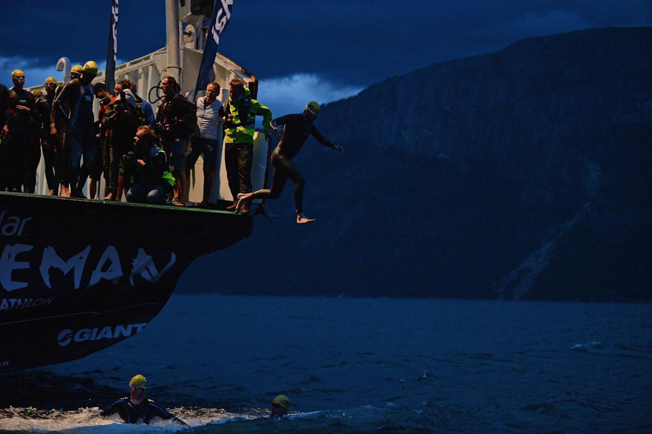 EIDFJORD, NORWAY - AUGUST 03: Athletes jump from a ferry into the Hardangerfjorden for the start of the Norseman Xtreme Triathlon on August 3, 2013 in Eodfjord, Norway. The race which was first held in 2003 runs point to point and is considered among many as the ultimate triathlon in the world. Owners and organisers Hardangervidda Triathlon Club limit the number of competitors to 250 they make their way through some of Norways most beautiful scenery during the course of the race. (Photo by Jeff J Mitchell/Getty Images)