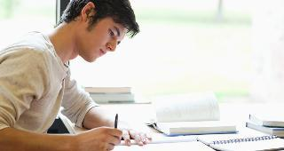 Young man writing at desk copyright wavebreakmedia/Shutterstock.com