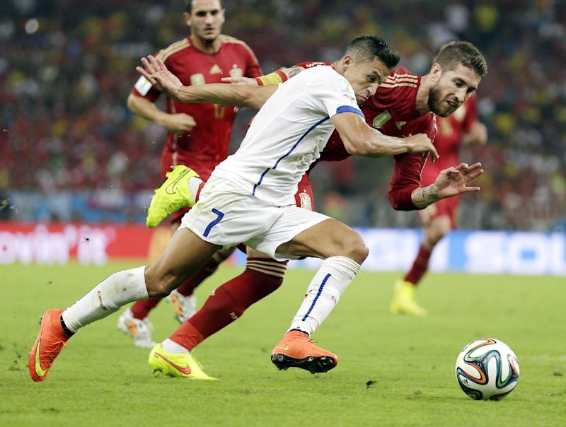Chile's Alexis Sanchez races against Spain's Sergio Ramos to get to the ball during the group B World Cup soccer match between Spain and Chile at the Maracana Stadium in Rio de Janeiro, Brazil, Wednesday, June 18, 2014