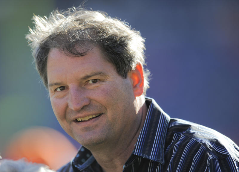 """In this Dec. 23, 2012 file photo, former Cleveland Browns quarterback Bernie Kosar stands on the sideline before of an NFL football game between the Browns and Denver Broncos, in Denver. Kosar believes he's been unfairly sacked as a TV broadcaster. Kosar contends he's been removed because of slurred speech he attributes to """"a direct result of the many concussions I received while playing in the NFL."""""""