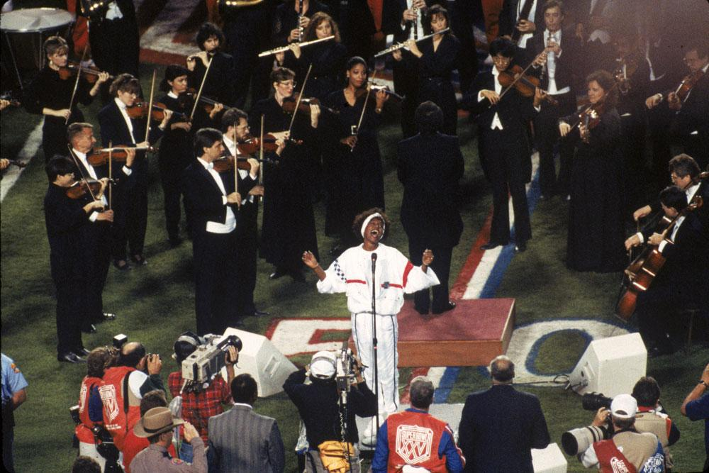 TAMPA, FL - JANUARY 27:  Singer Whitney Houston sings the National Anthem before the New York Giants took on the Buffalo Bills in Super Bowl XXV at Tampa Stadium on January 27, 1991 in Tampa, Florida. The Giants defeated the Bills 20-19. (Photo by Gin Ellis/Getty Images)