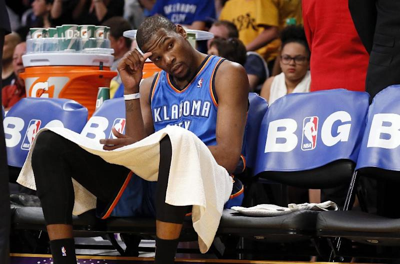 Oklahoma City Thunder forward Kevin Durant sits down on the bench as his team trails the Los Angeles Lakers after the third quarter of an NBA basketball game in Los Angeles, Sunday, March 9, 2014. The Lakers won 114-110