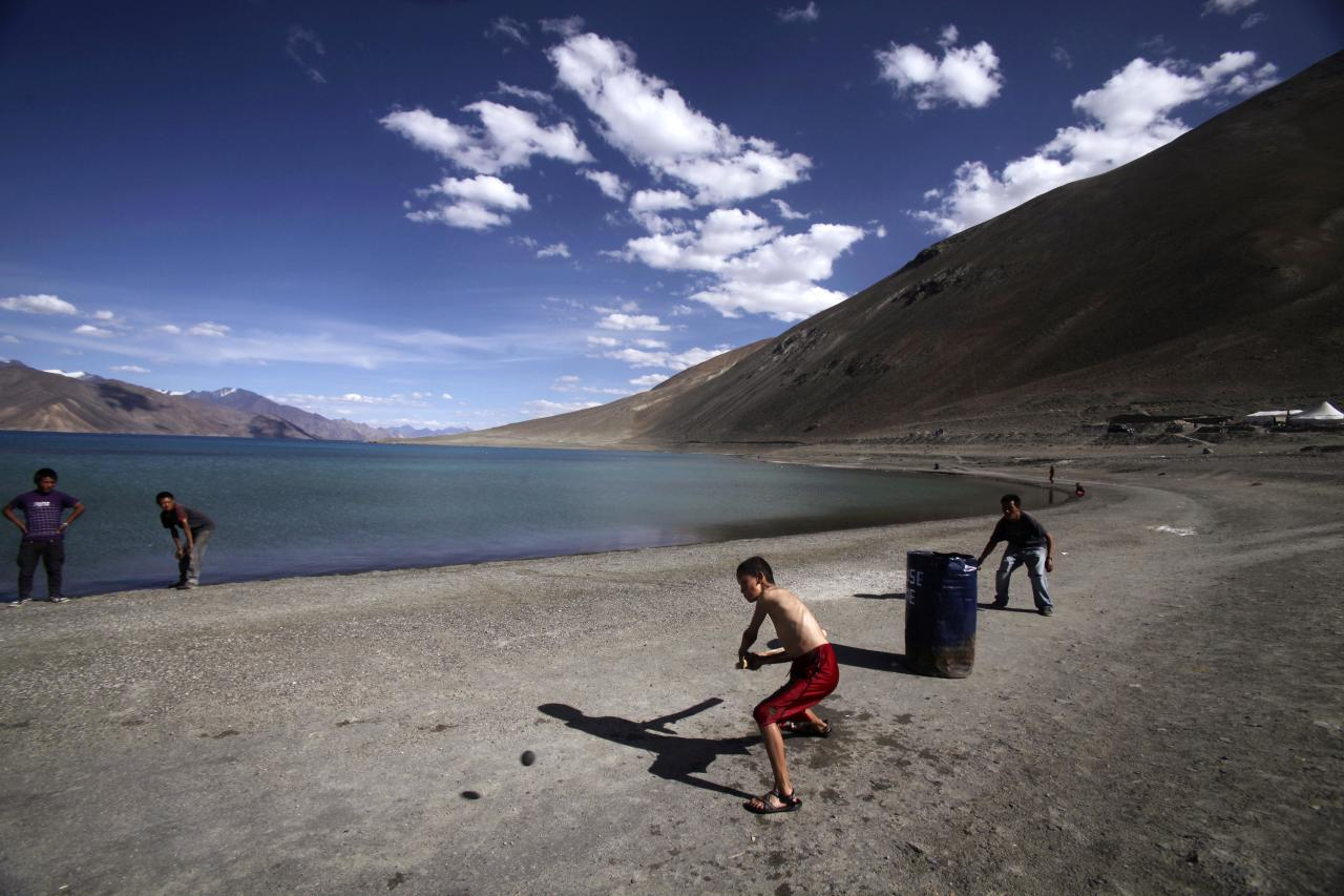 In this Friday, July 22, 2011 photo, children play cricket near Pangong Lake, near the India-China border in Ladakh, India. Ladakh is a remote part of the former princely state of Kashmir, which is at the heart of the six-decade conflict between nuclear-armed neighbors India and Pakistan. While Kashmir is best known for the Indo-Pakistani standoff, part of Ladakh, an ethnically distinct region with historical ties to Tibet, has been controlled by China for decades. (AP Photo/Channi Anand)