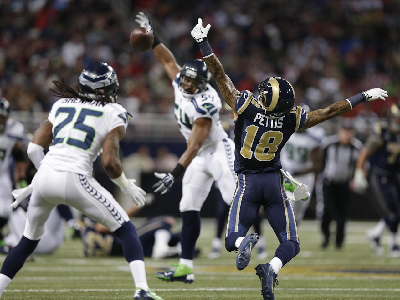 St. Louis Rams wide receiver Austin Pettis (18) cannot make a catch during the first half of an NFL football game against the Seattle Seahawks, Monday, Oct. 28, 2013, in St. Louis. Seattle Seahawks cornerback Richard Sherman (25) made the interception on the play. (AP Photo/Michael Conroy)