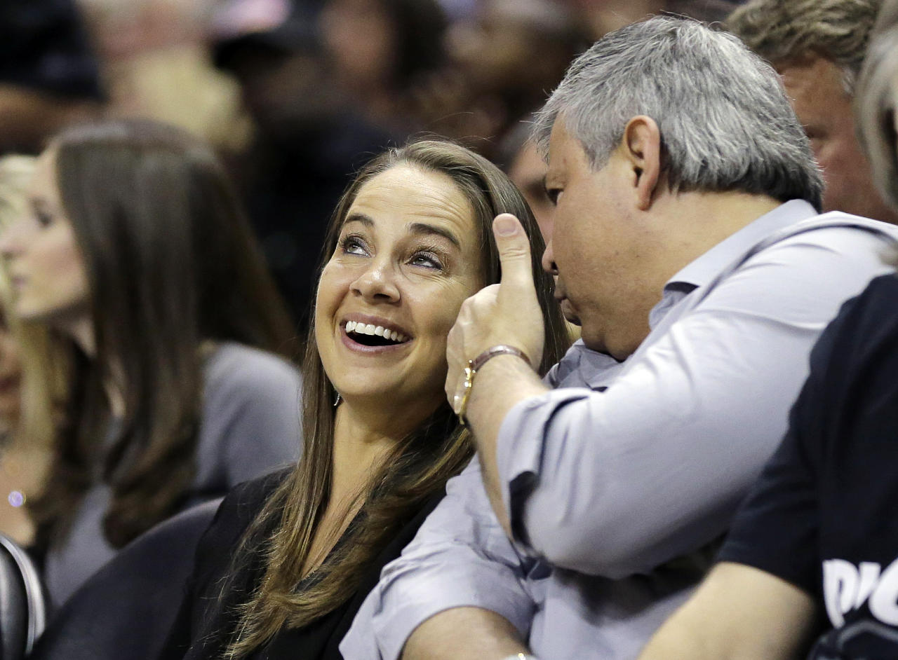 In this April 30, 2014 photo, San Antonio Stars' Becky Hammon, left, attends Game 5 of the opening-round NBA basketball playoff series between the Spurs and Dallas Mavericks in San Antonio. Gregg Popovich said that he believes Hammon and other women can cross over and coach men, even in the NBA. (AP Photo/Eric Gay)