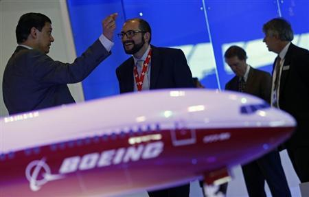 Visitors talk next to a Boeing 777X aircraft model at the Singapore Airshow