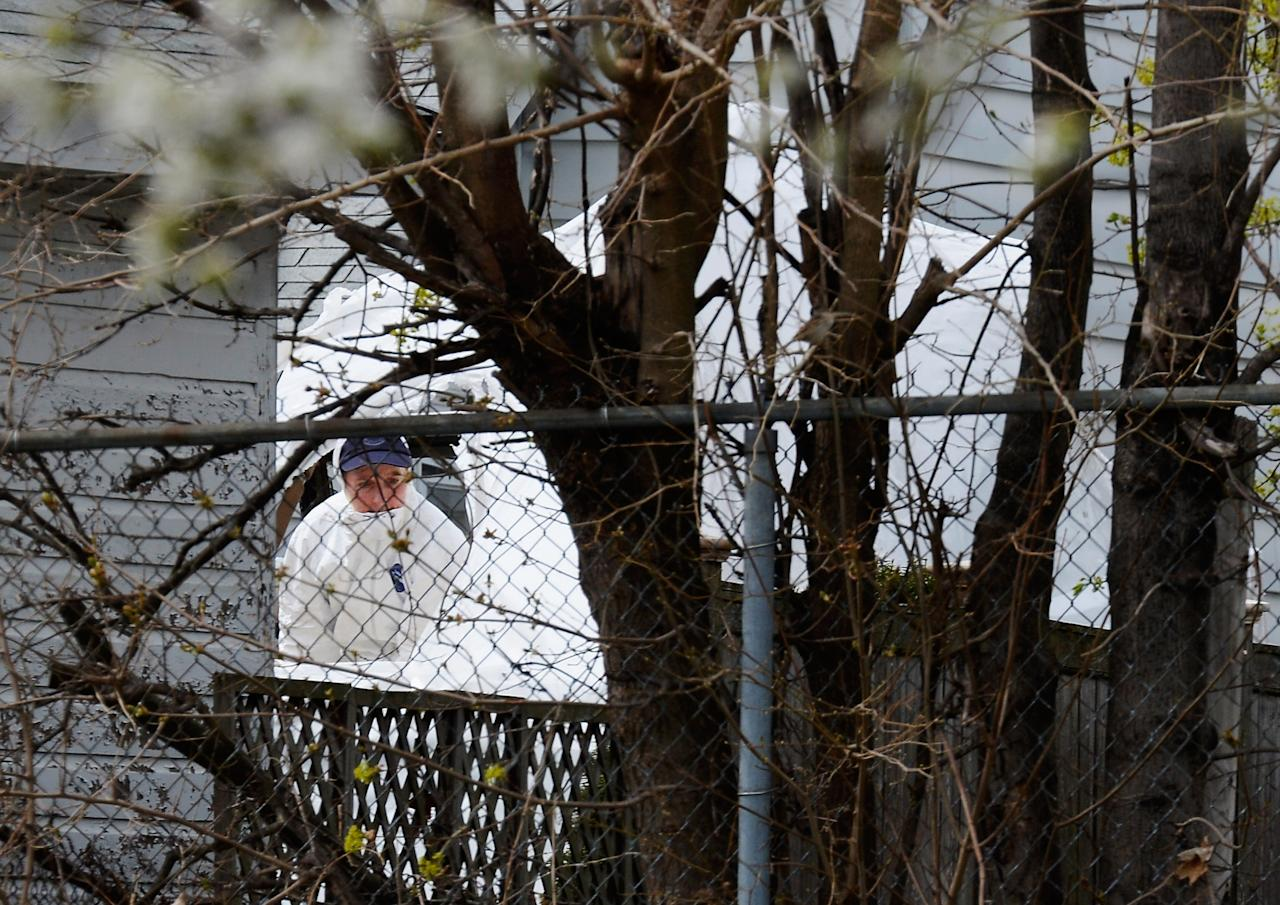 WATERTOWN, MA - APRIL 20:  An FBI investigator wearing white overalls stands inside the boat where bombing suspect was hiding from police on Franklin Street on April 20, 2013 in Watertown, Massachusetts. A manhunt for Dzhokhar A. Tsarnaev, 19, a suspect in the Boston Marathon bombing ended after he was apprehended on a boat parked on a residential property in Watertown, Massachusetts. His brother Tamerlan Tsarnaev, 26, the other suspect, was shot and killed after a car chase and shootout with police. The bombing, on April 15 at the finish line of the marathon, killed three people and wounded at least 170  (Photo by Kevork Djansezian/Getty Images)
