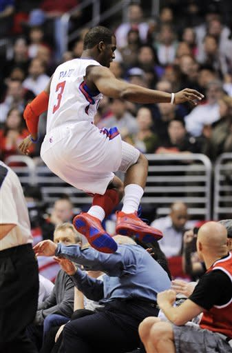 Los Angeles Clippers guard Chris Paul jumps over the first row of fans while chasing a ball out of bounds during the first half of their NBA basketball game against the Portland Trail Blazers, Friday, March 30, 2012, in Los Angeles. (AP Photo/Mark J. Terrill)