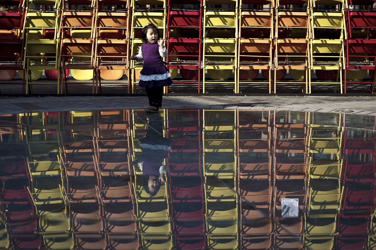 A girl is reflected on a glass panel as she plays in front of an art structure formed by chairs on display.